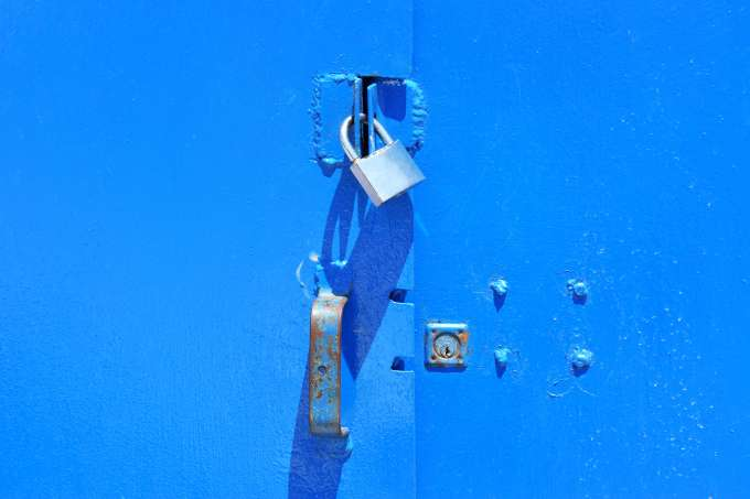 A silver padlock on a painted blue metal door