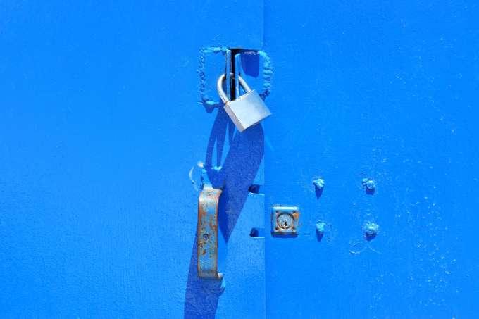 A silver padlock on a painted blue metal door